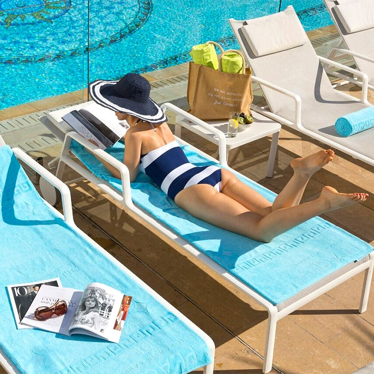 Young woman sunbathing on a deckchair at the luxury hotel Le Majestic Barrière in Cannes, French Riviera