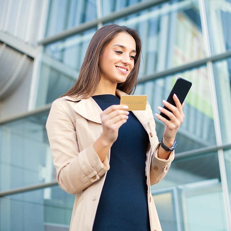 Jeune femme commandant une villa avec sa carte de crédit