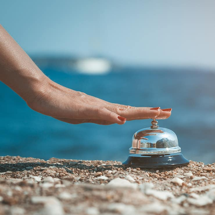 Close-up of a woman's hand ringing a service bell on an ocean background
