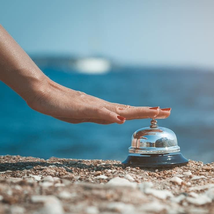Gros plan d'une main féminine sonnant une cloche de service sur fond d'océan