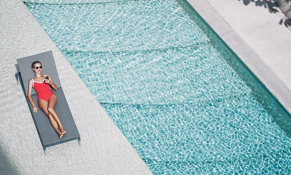 Jeune femme en maillot de bain sur un transat près de la piscine d'une villa de luxe